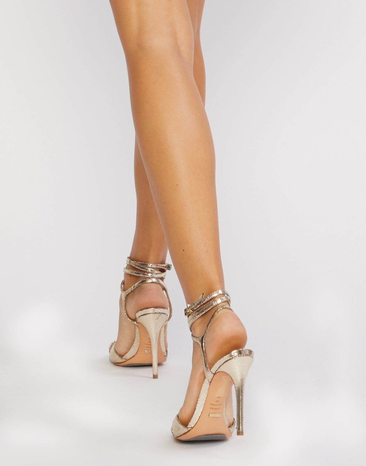 Back view of gold metallic stiletto heels with ankle straps