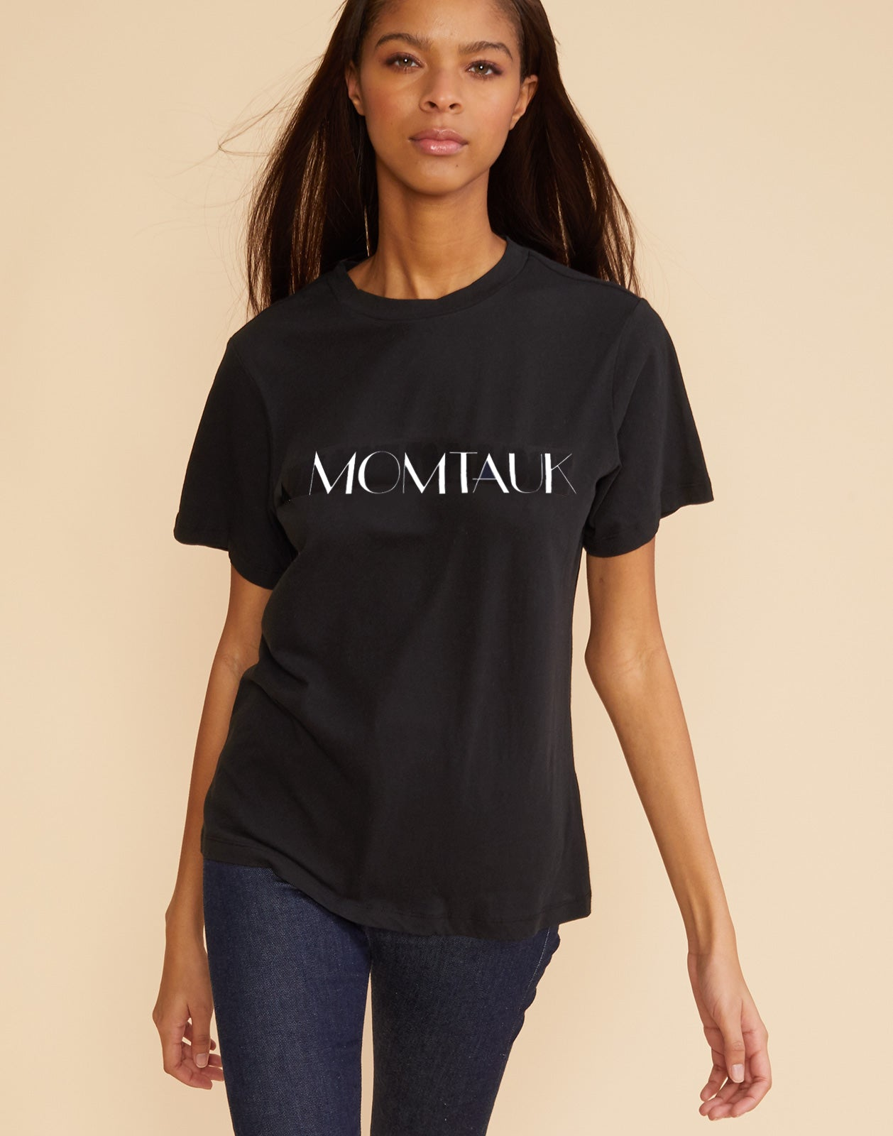 Close view of model wearing a black t-shirt with 'momtauk' printed across the front