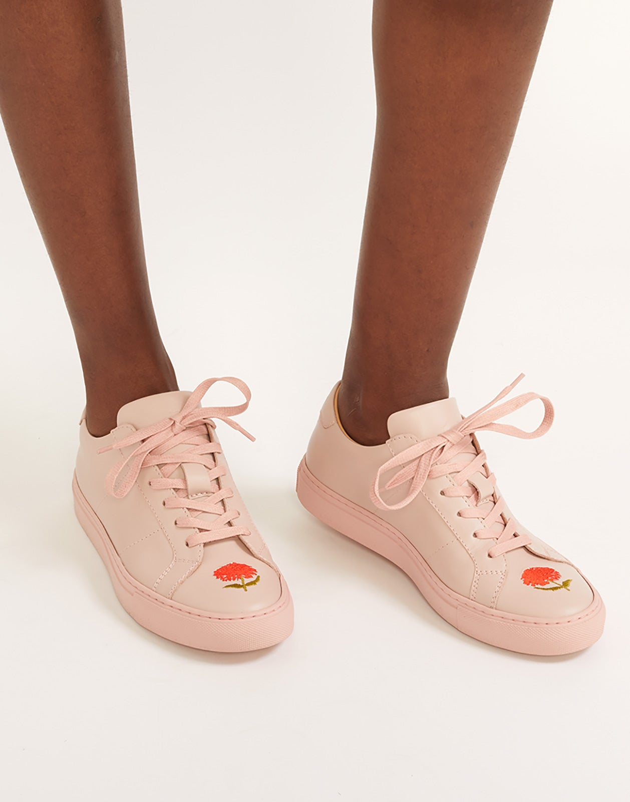 Alternate close view of pink lace up sneaker with flower embroidery.