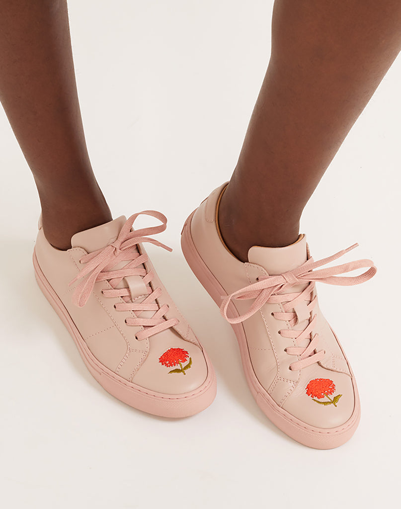 Close view of soft leather lace up sneaker with flower embroidery.