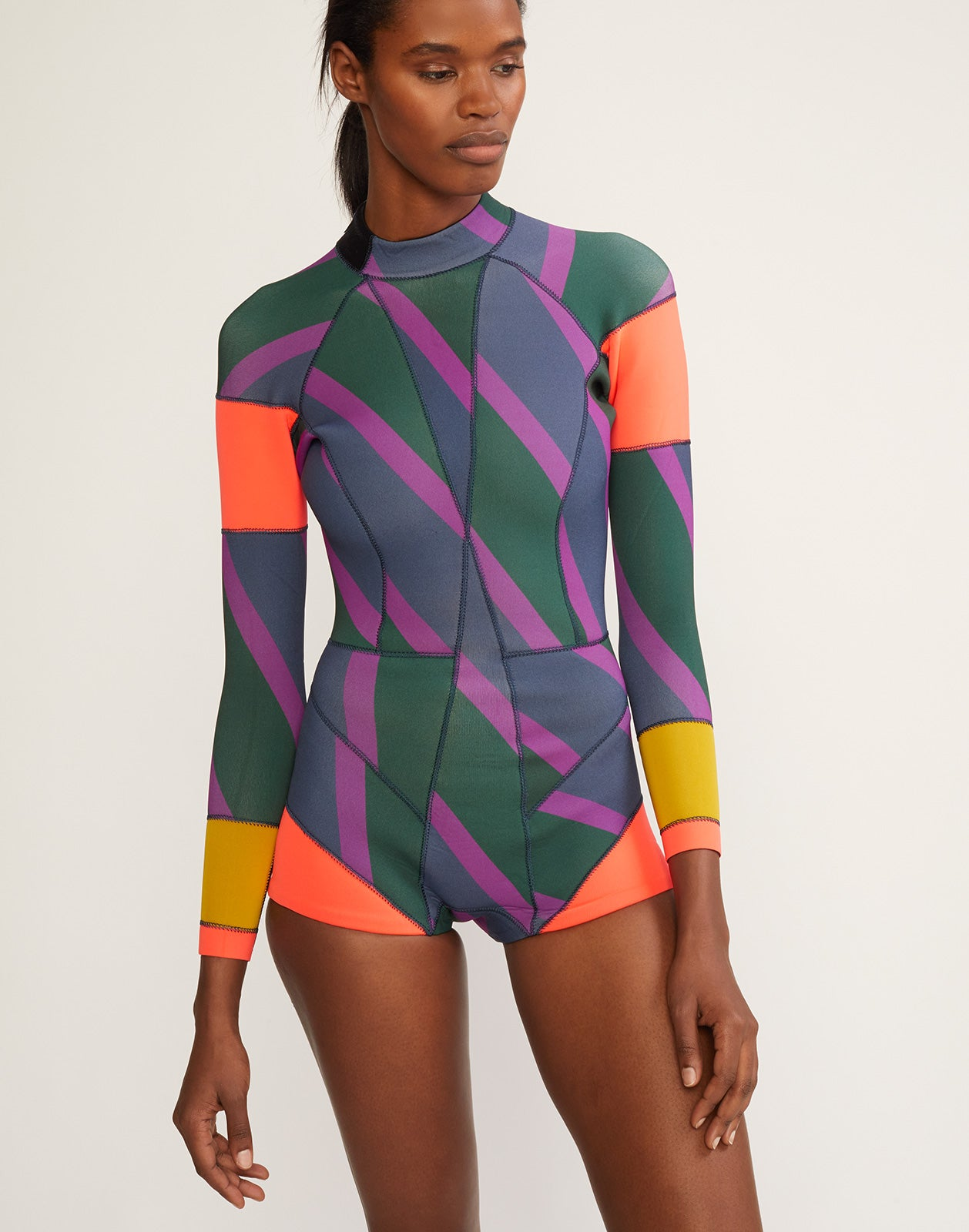 Cropped front view of Zig Zag stripe wetsuit in olive and purple with neon orange colorblock details.