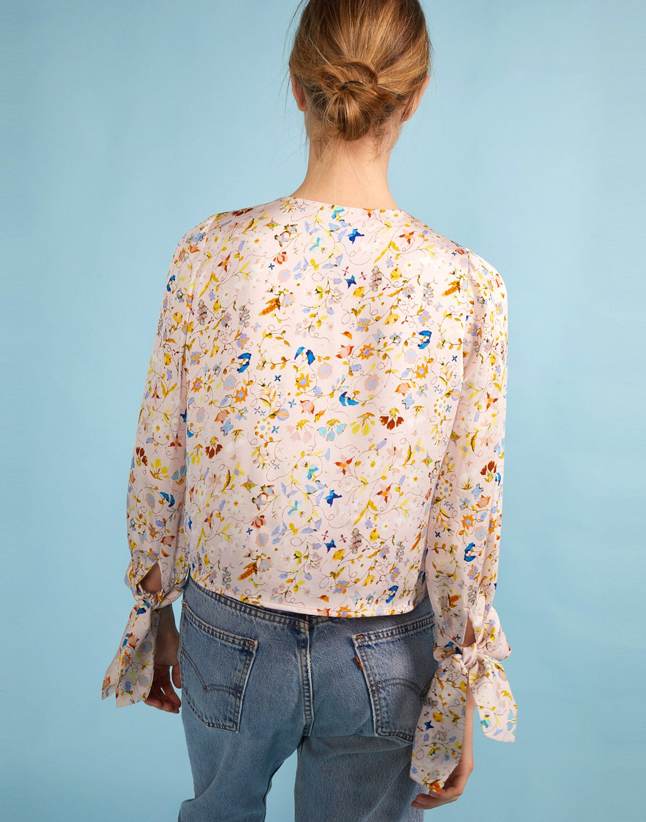 Close up back view of model wearing Tennessee Tie Front Top in magic garden.