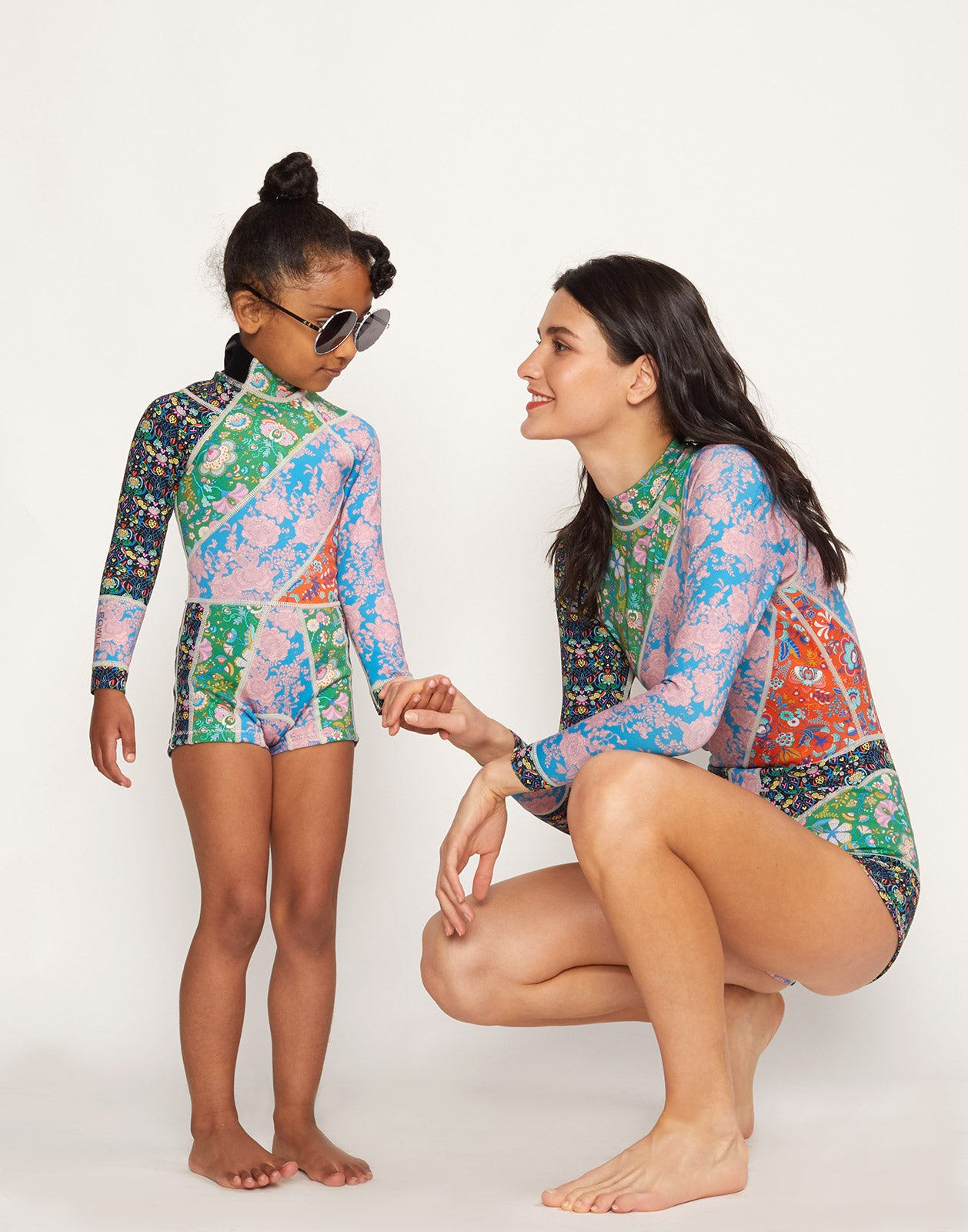 Full view of model wearing Girl's Floral Wetsuit with another model in Daybreak Floral Wetsuit.
