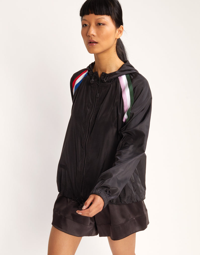 Close front view of moel walking in the Serena windbreaker with colorblock stripe detail.