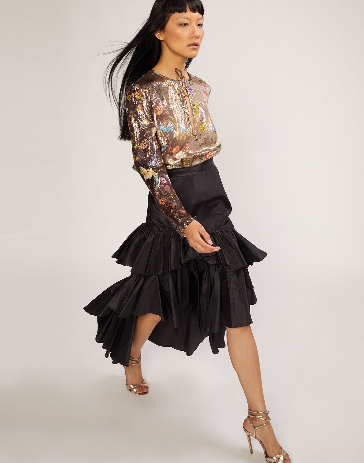 Model walking in black silk taffeta skirt with asymmetrical cascading ruffles.