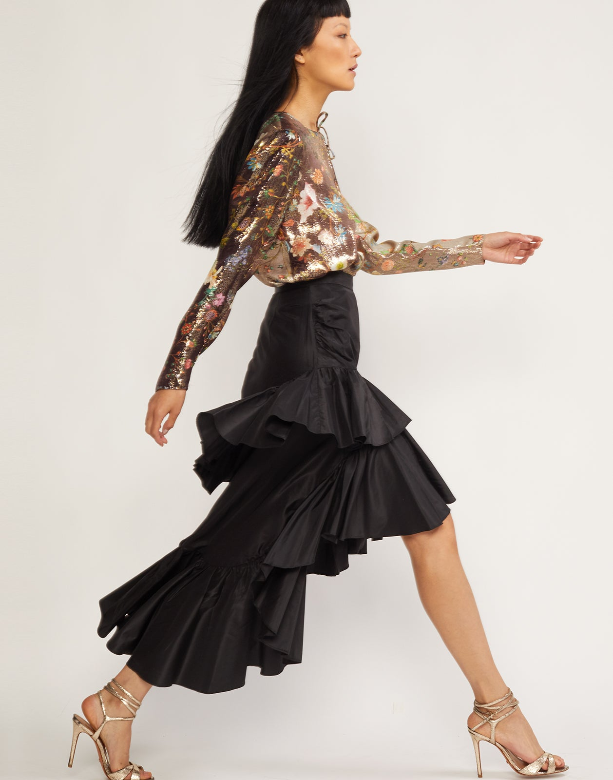 Side view of model wearing teh Camila tiered ruffle skirt in black.