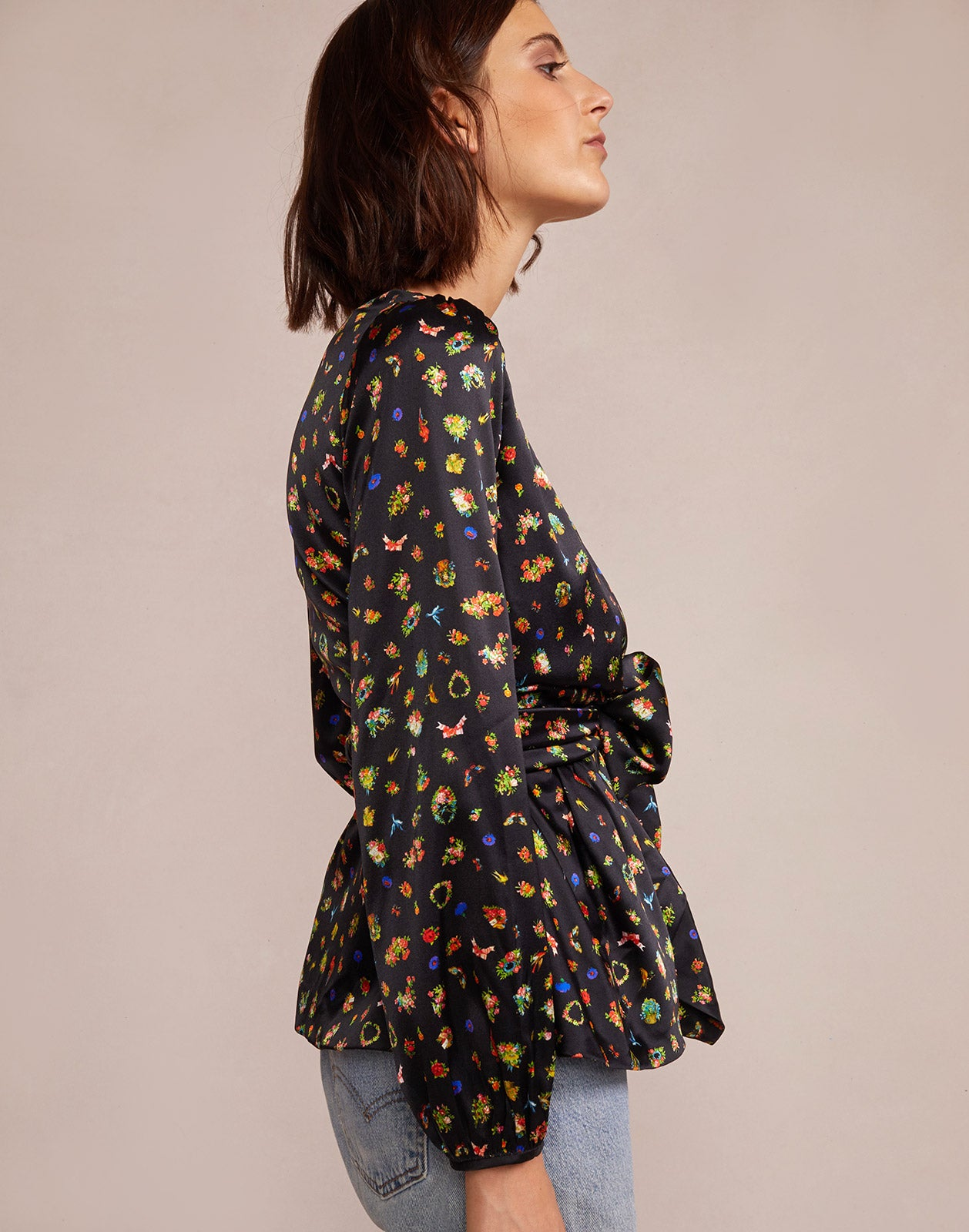 Side view of Mila Silk Wrap Blouse with mini flower, bird, and butterflies print.