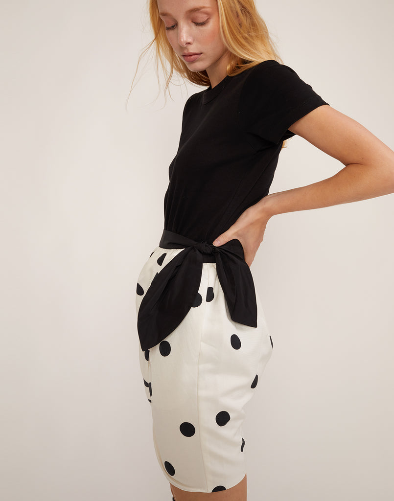 Side view of model in the black and white polka dot print Emery skirt.