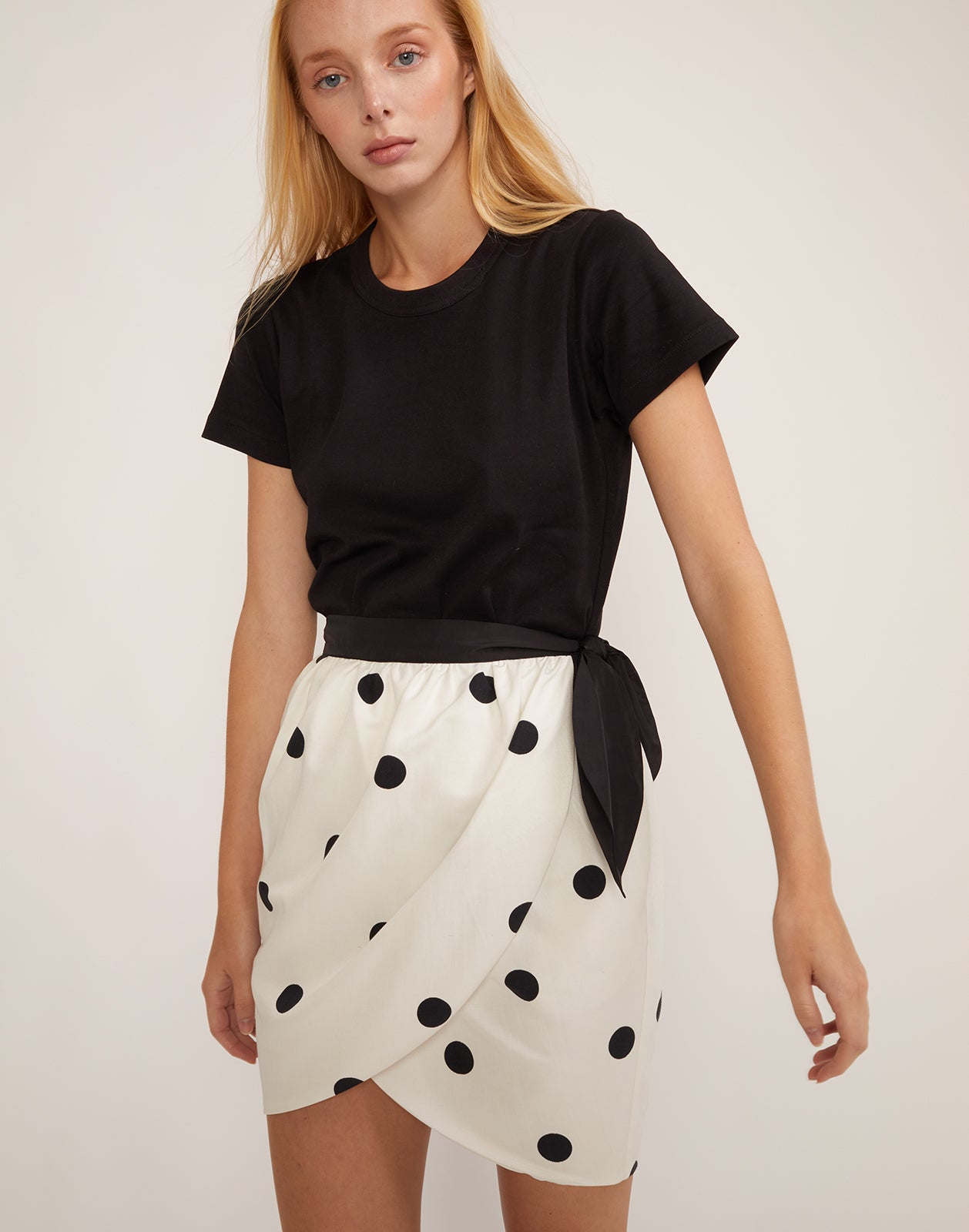 Front view of model in the black and white polka dot print Emery skirt.