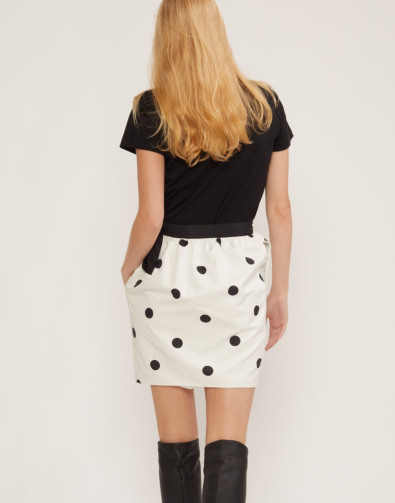 Back view of model in the black and white polka dot print Emery skirt.