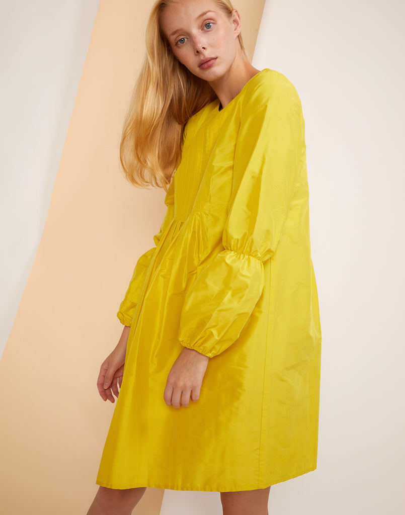 Close view of model in the yellow silk taffeta Havana Pintuck Dress