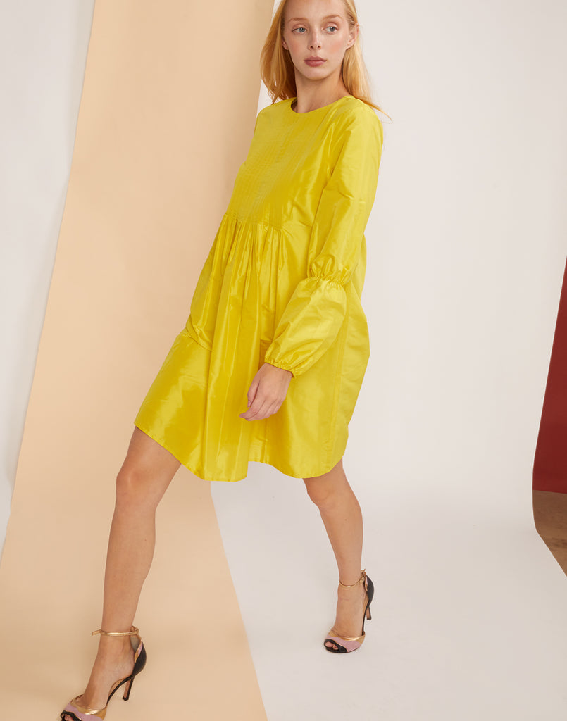 Full view of model walking in the Havana Pintuck dress in yellow taffeta.