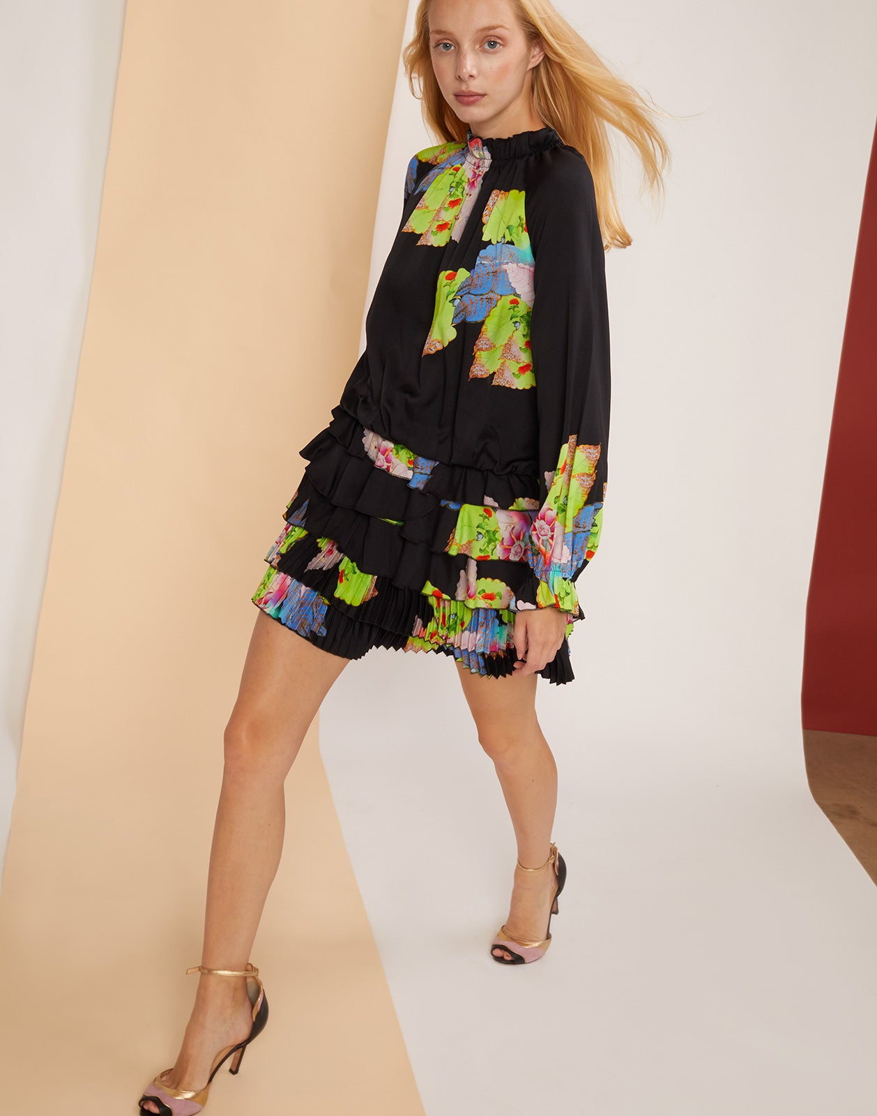 Diagonal view of model walking in the Amalfi Floral Leaf Mini Dress with hair blowing.
