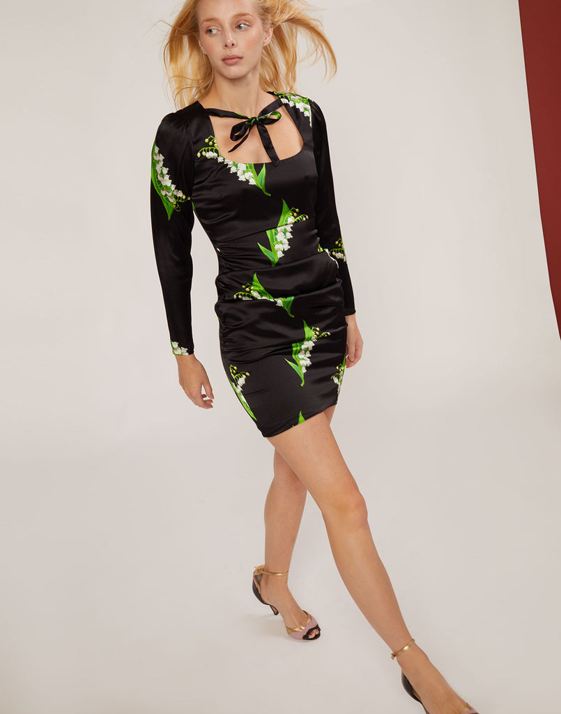 Front view of model stepping forward wearing black printed Apollo Lily of the Valley Tie Neck Dress.