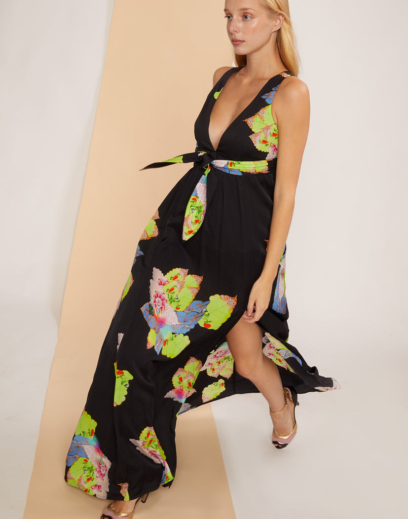 Side view of model walking in the Aurora Maxi Dress with full skirt and slit exposing leg.