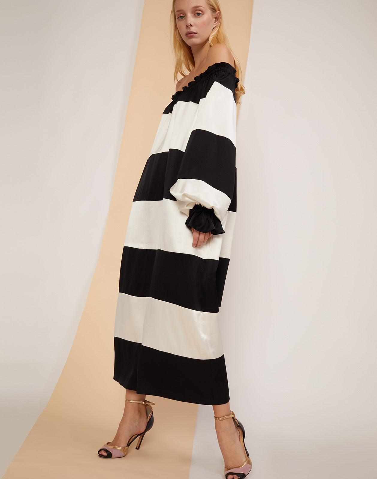 Three quarter view of the Shanley off shoulder black and white striped dress.