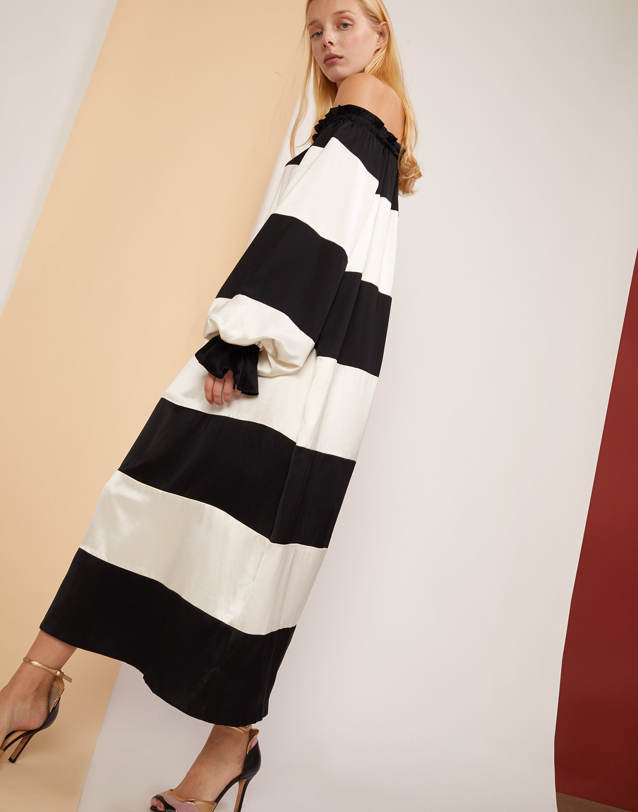 Side view of the Shanley off shoulder black and white striped dress.