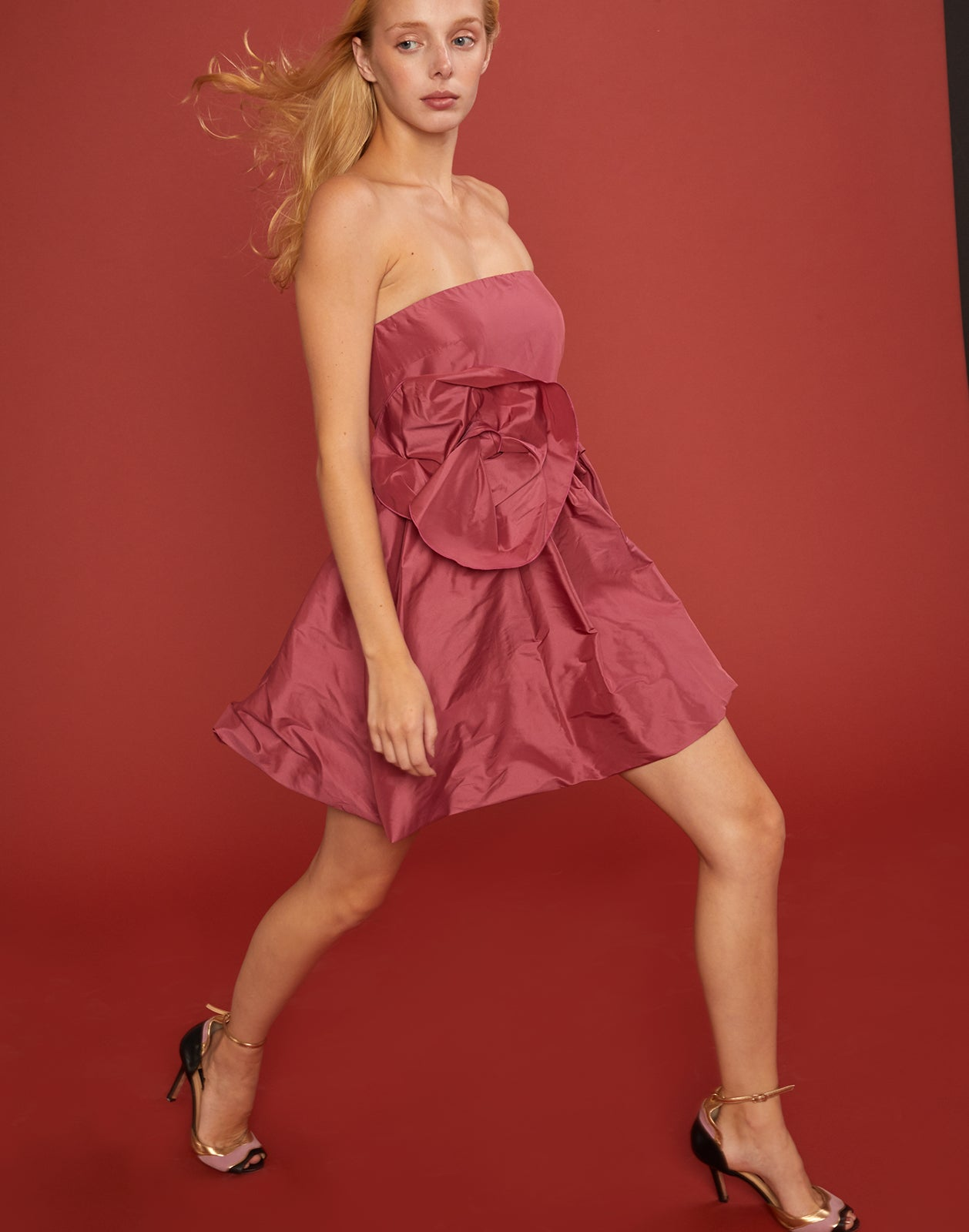 Diagonal walking shot of Lulu Dress with oversized bow detail at waist