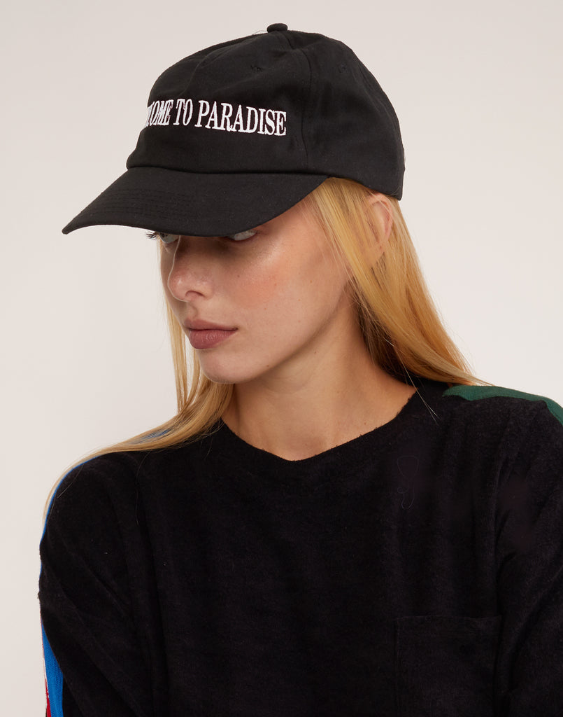 Side view of Welcome to Paradise hat with white stitched lettering.