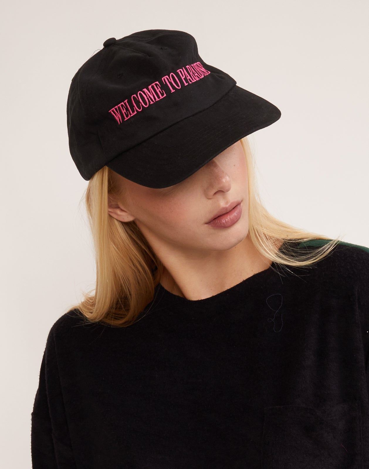 Model wearing the Welcome to Paradise baseball cap with pink stitched lettering.