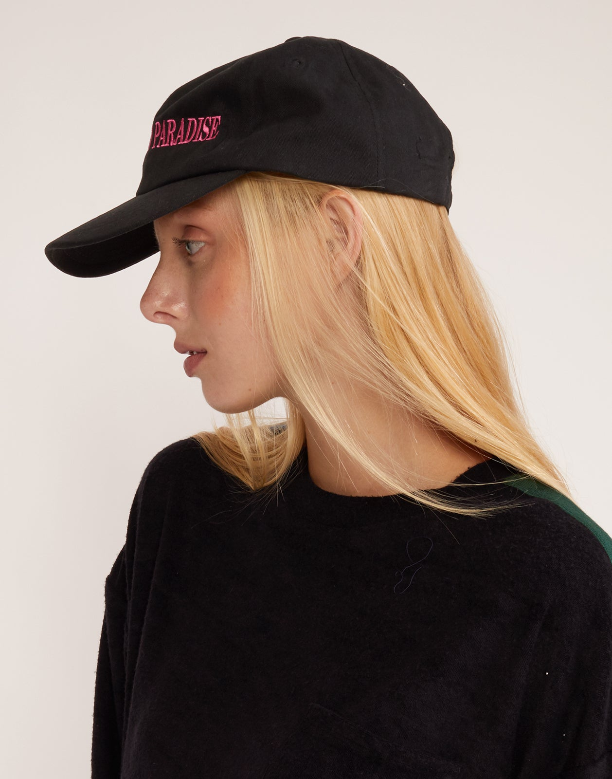 Side view of the Welcome to Paradise hat in black twill with pink embroidery.