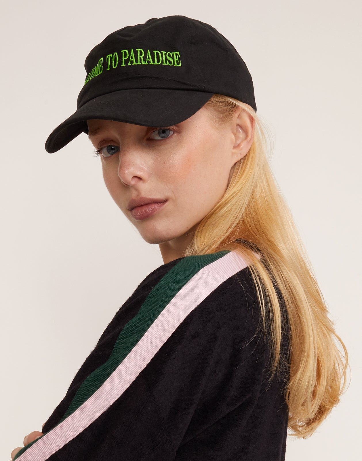 Three quarter view of model wearing the 'Welcome to Paradise' baseball cap with green stitching.