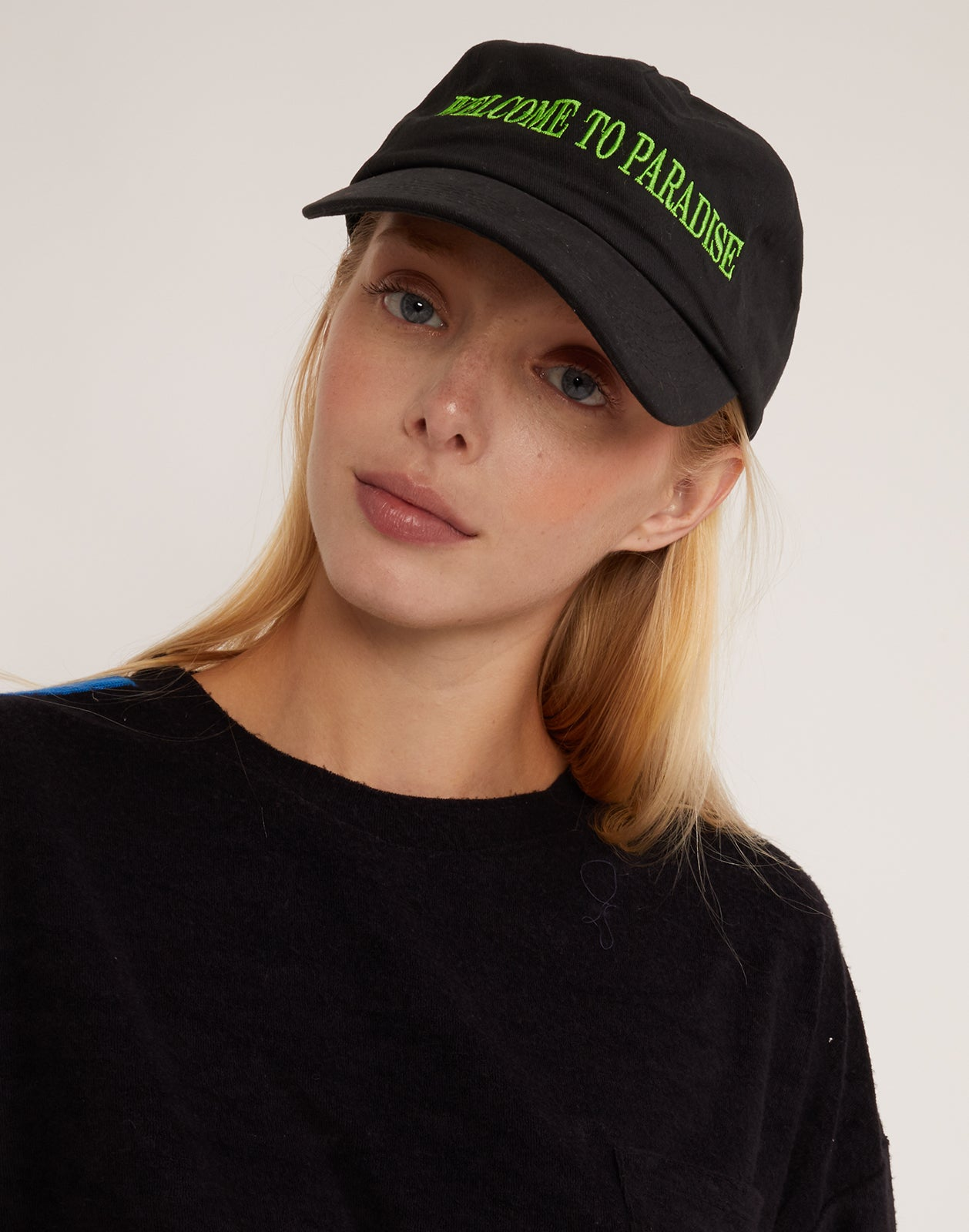 Model wearing a black baseball cap with green 'welcome to paradise' baseball hat.