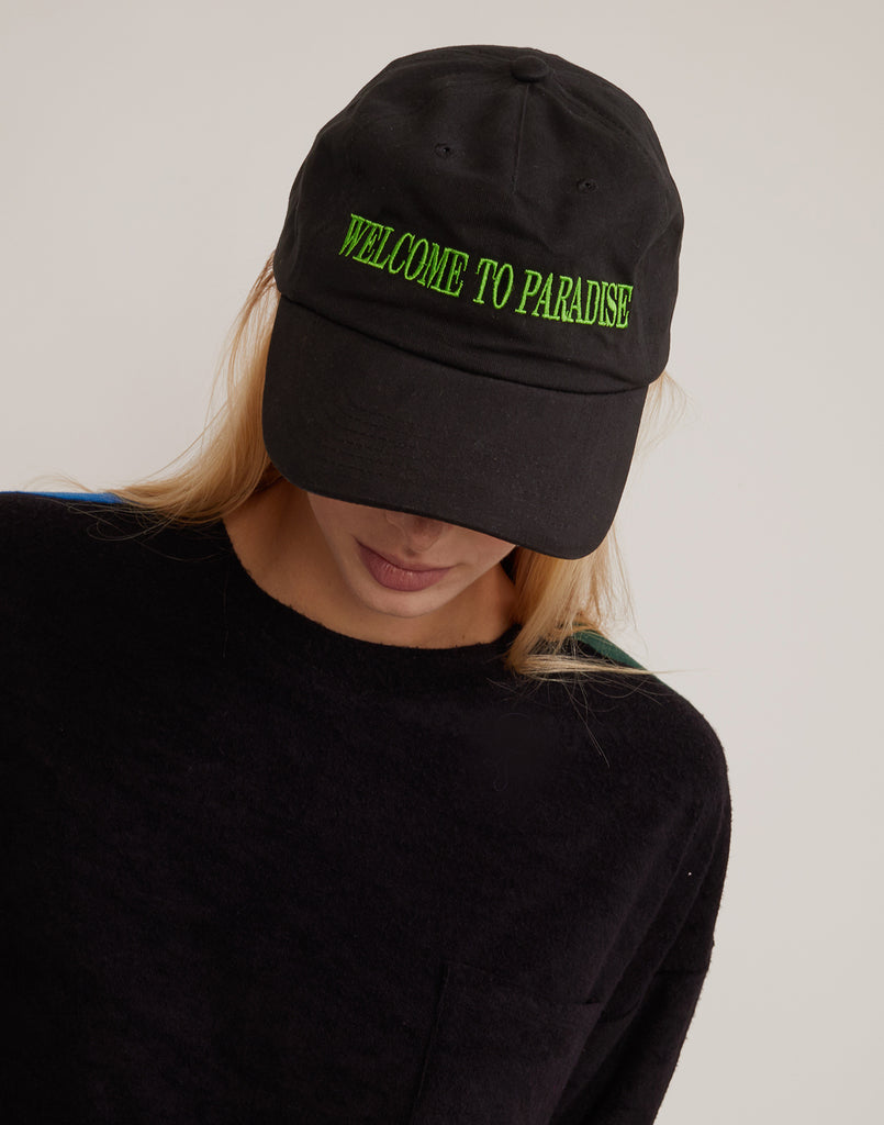 Welcome to Paradise baseball hat with green embroidered lettering.