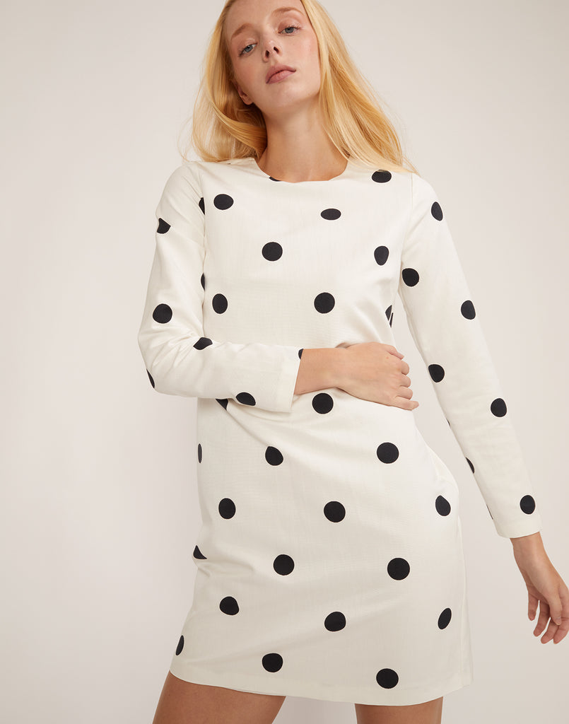 Front view of model walking in the black and white polka dot print dress.