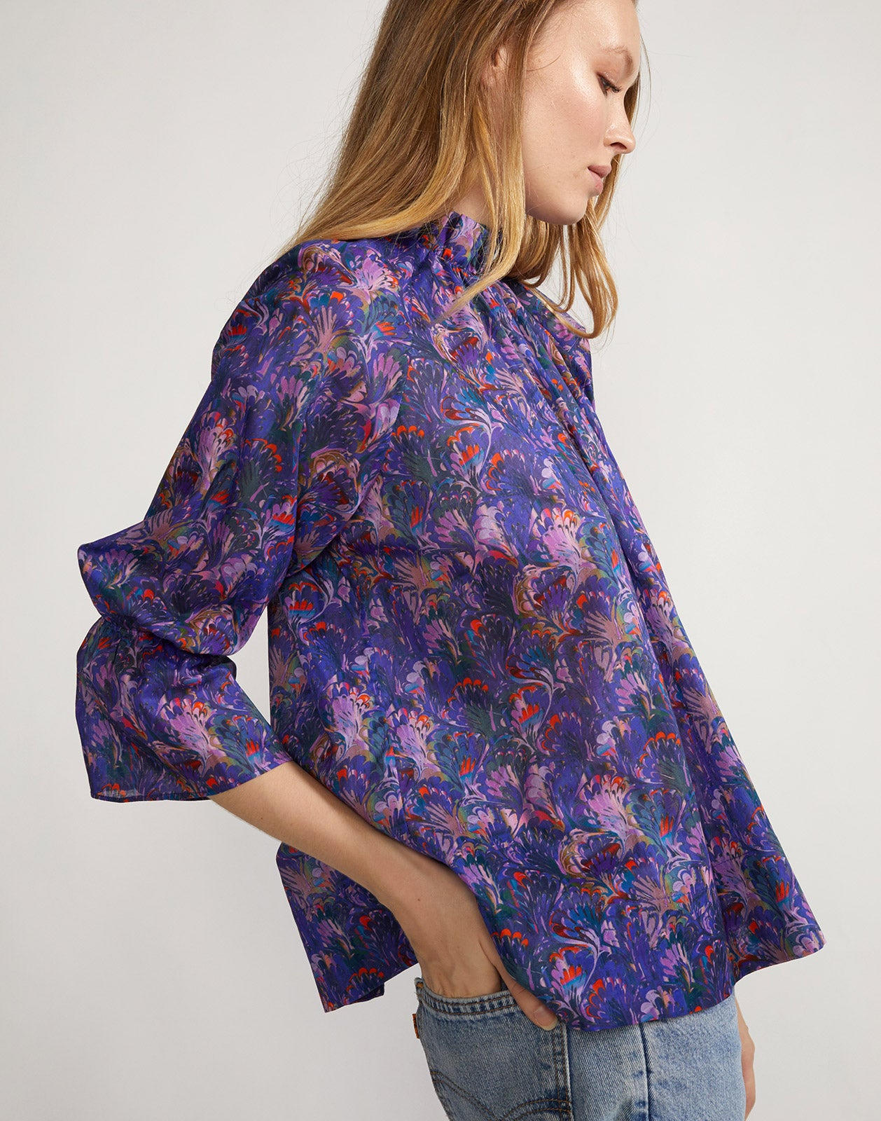 Side view of cotton smocked top with wide length hem