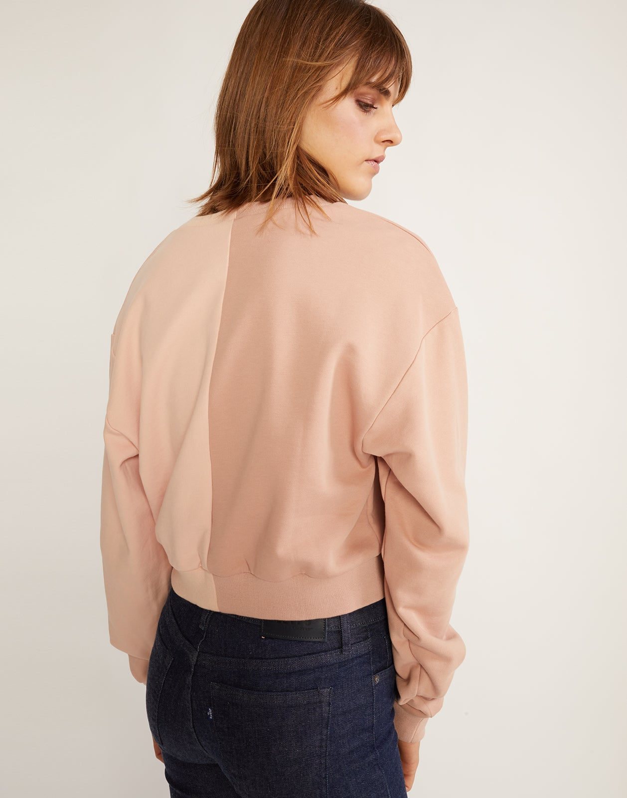 Back view of the half beige, half pink caliyork cropped sweatshirt in soft cotton.