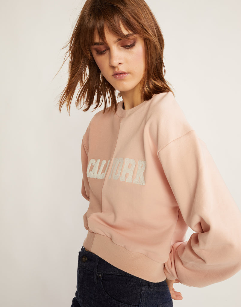 3/4 angled view of the half beige, half pink caliyork cropped sweatshirt in soft cotton.