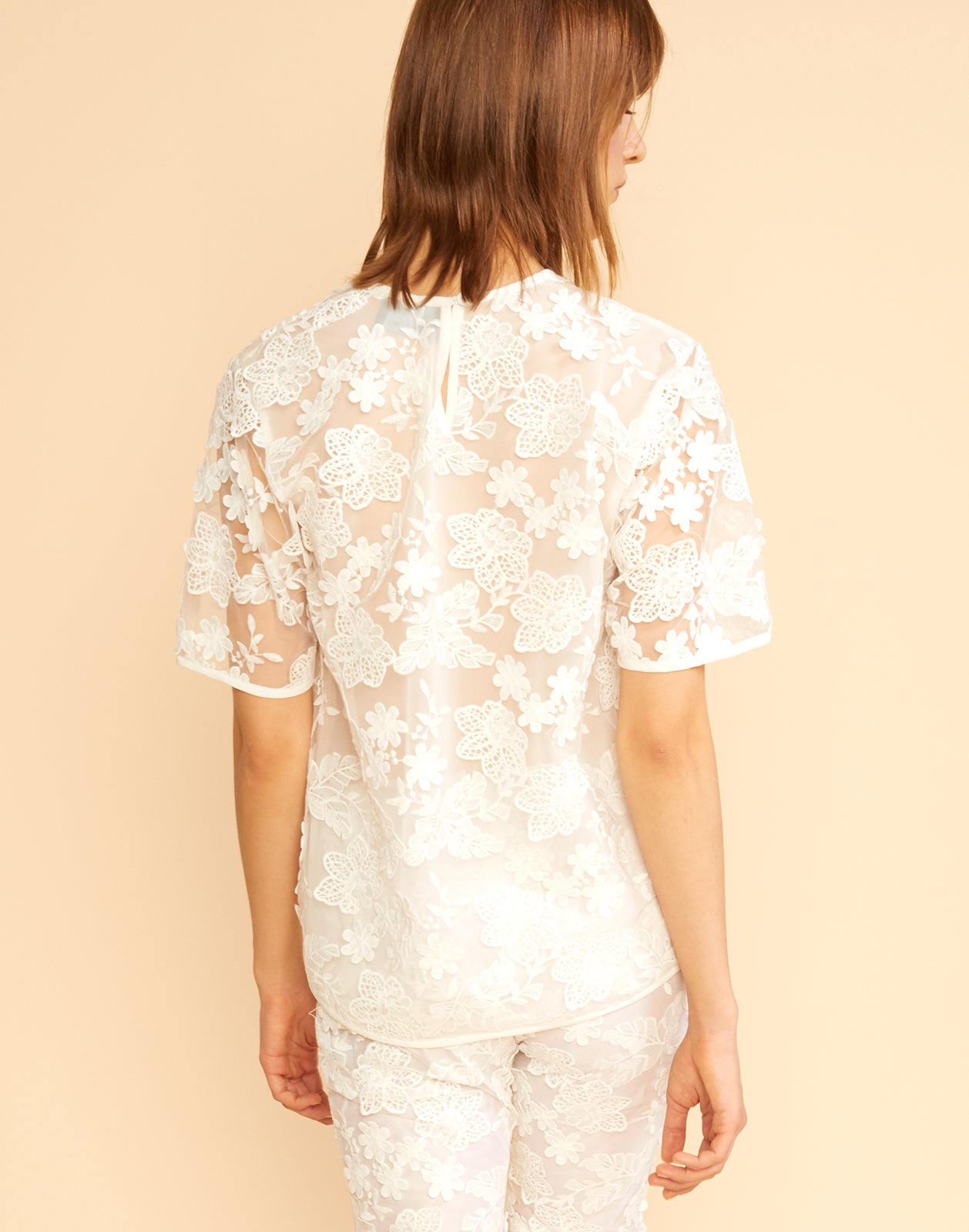 Back view of sheer floral lace tee.