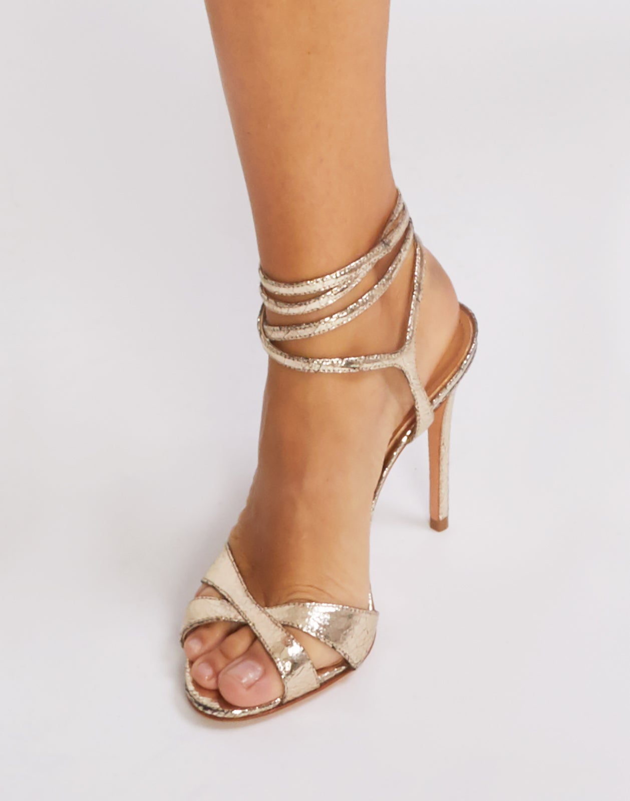 Front view of gold metallic stiletto heels with ankle straps