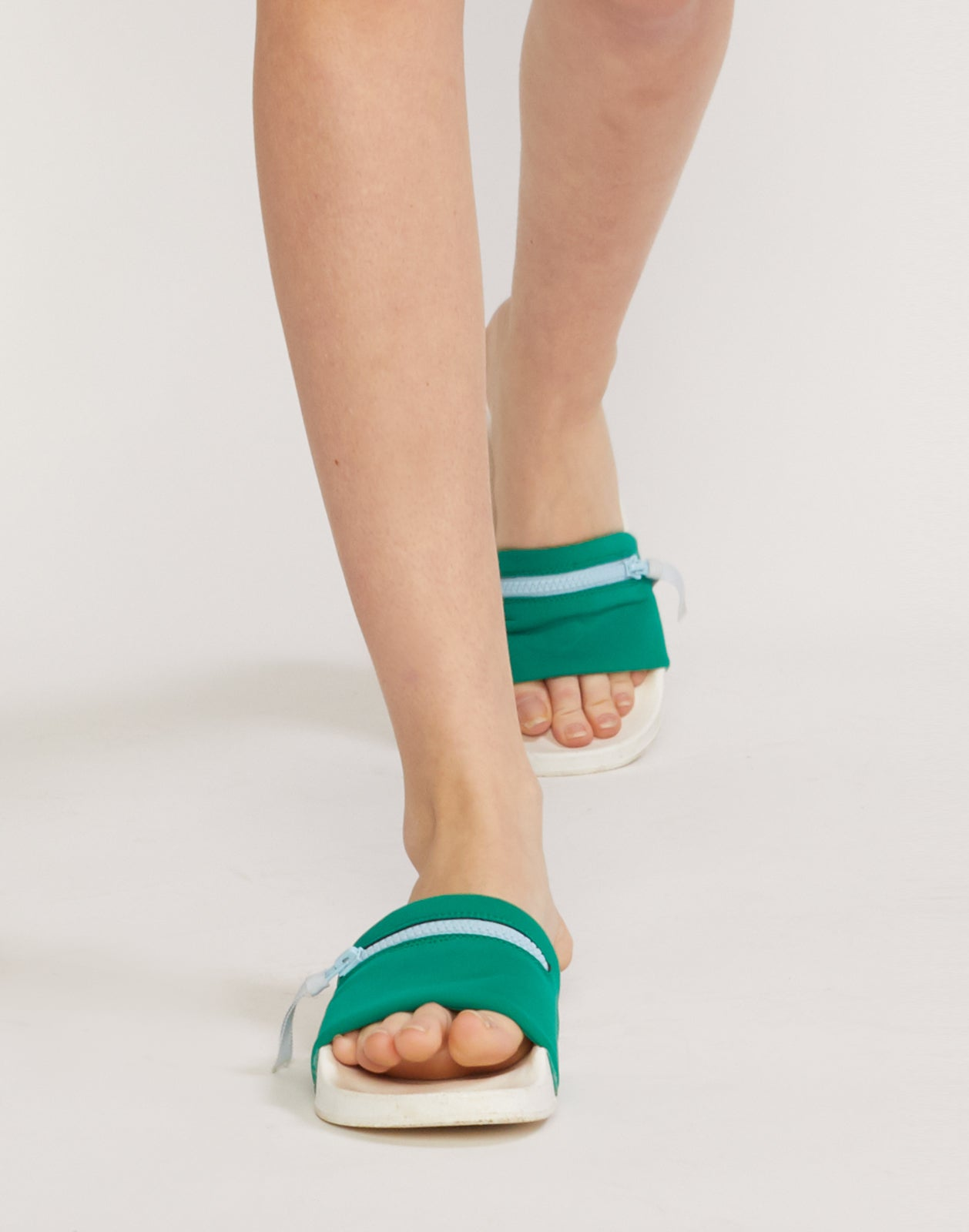 Front view of green neoprene slide sandals on model.