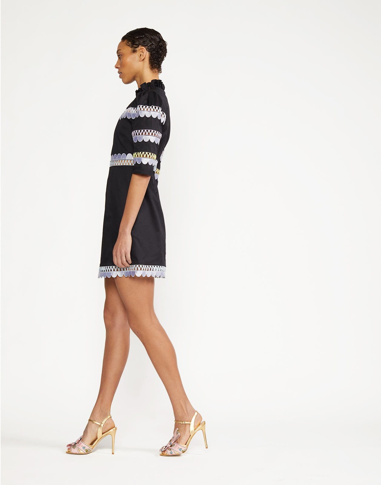 Side view of embroidered ruffle dress with fitted torso.