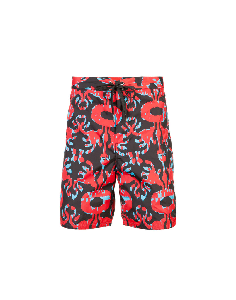 Product image of board shorts in abstract navy and bright red print.