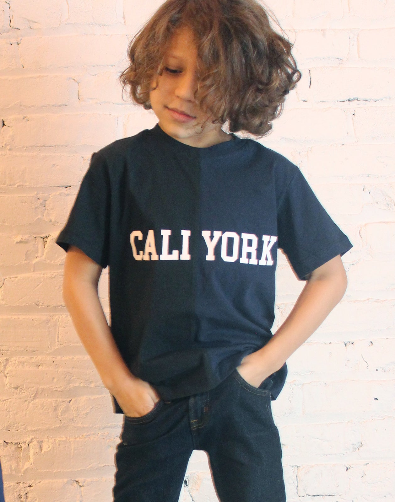 Close view of the kid's CaliYork t-shirt in half navy, half black.