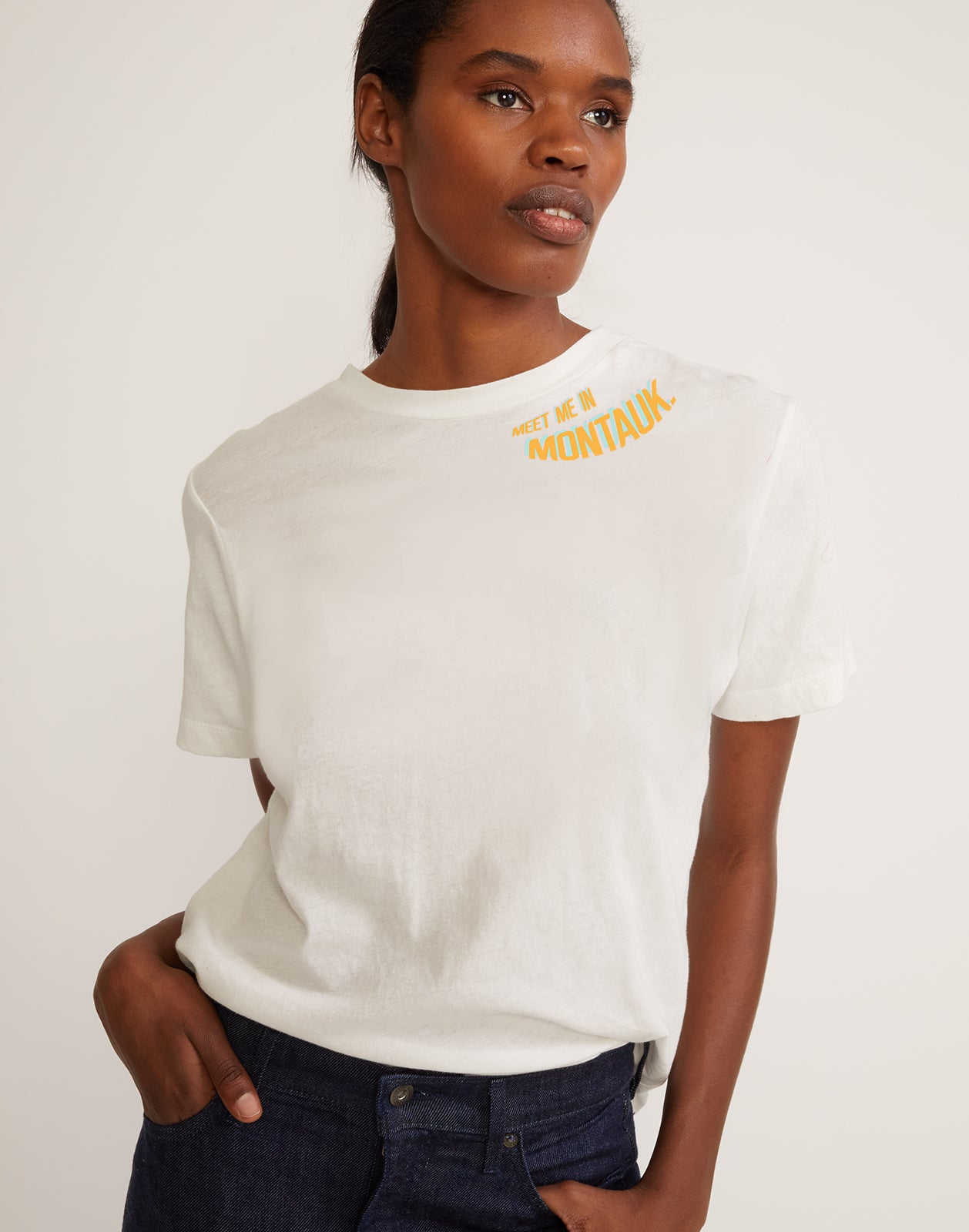 Meet me in Montauk Tee in white cotton with yellow and light blue printed lettering.