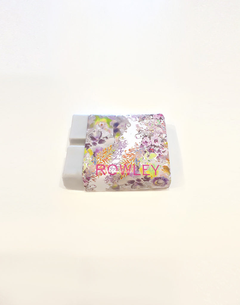 Rowley surfwax with light floral print wrapper pulled away from wax.
