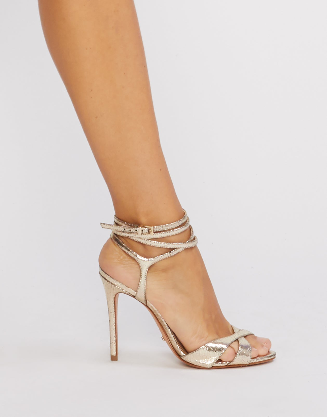 Side view of gold metallic stiletto heels with ankle straps