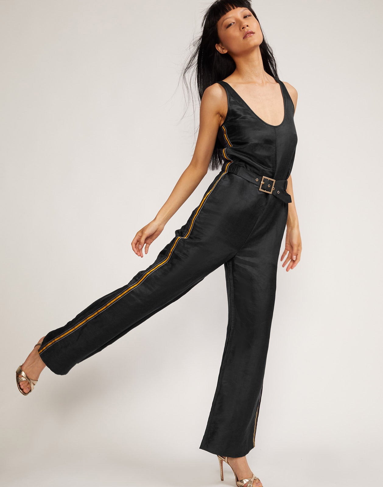 Model with leg swinging back in the black silk linen Dylam jumpsuit with belted waist.
