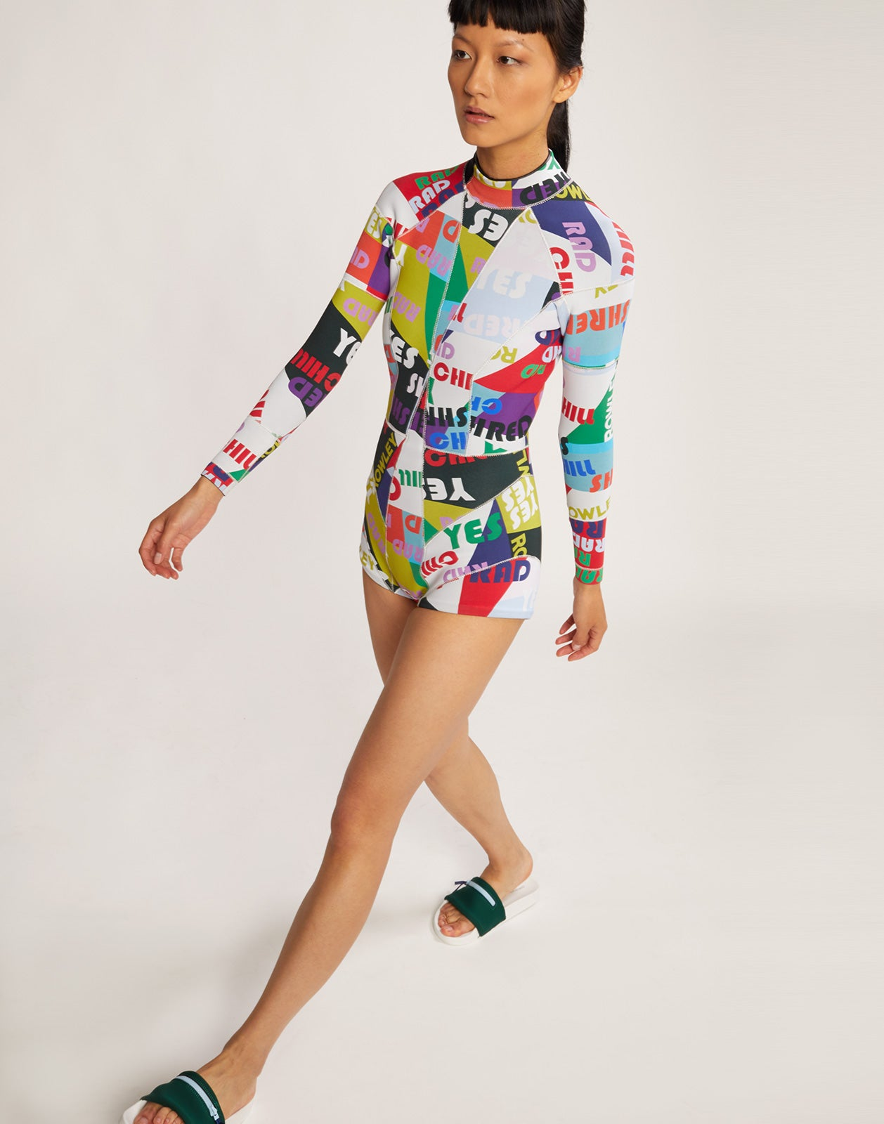 Model walking in the Good Vibes neoprene wetsuit in good vibes graphic words print.