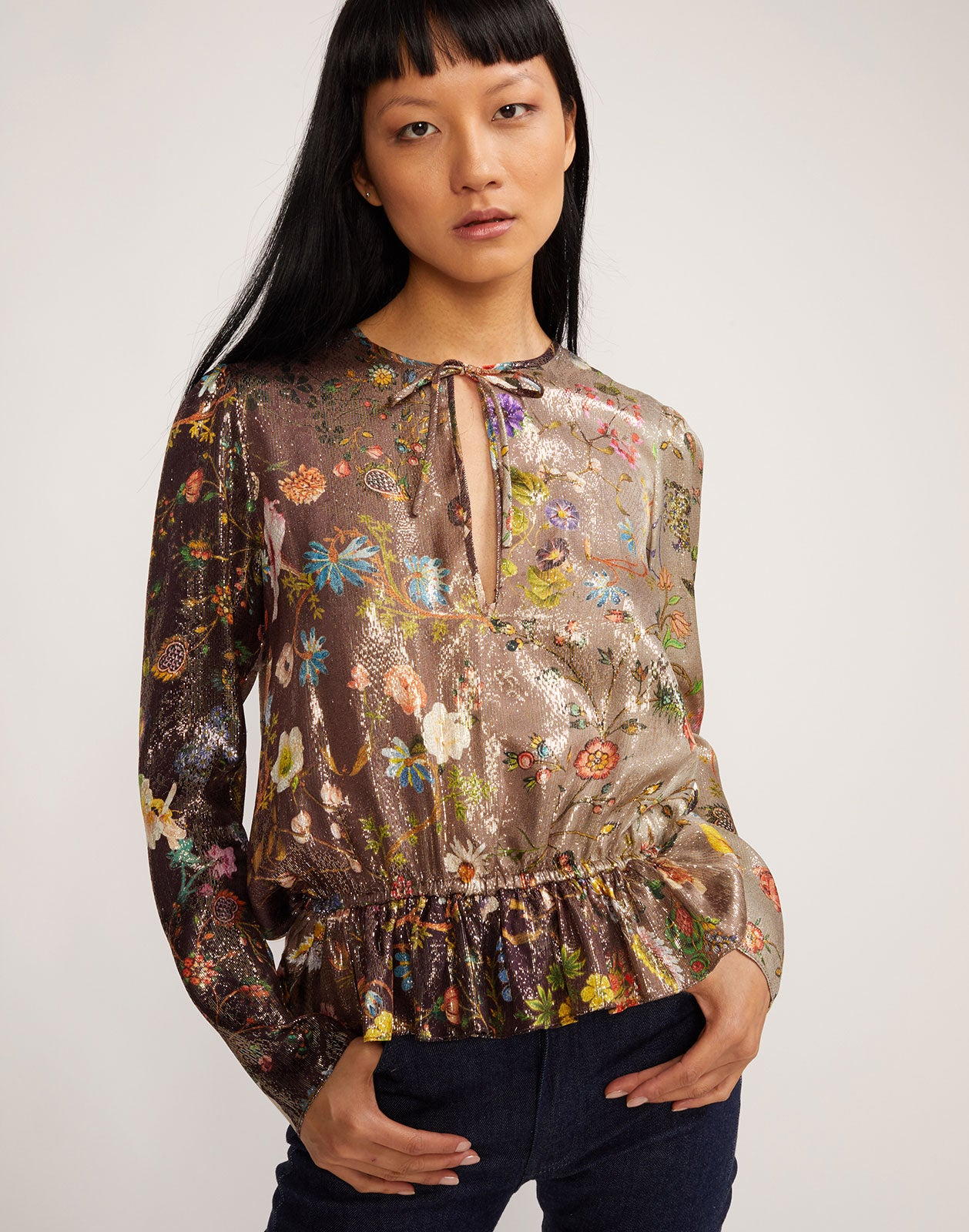Front view of metallic floral blouse with ruching.