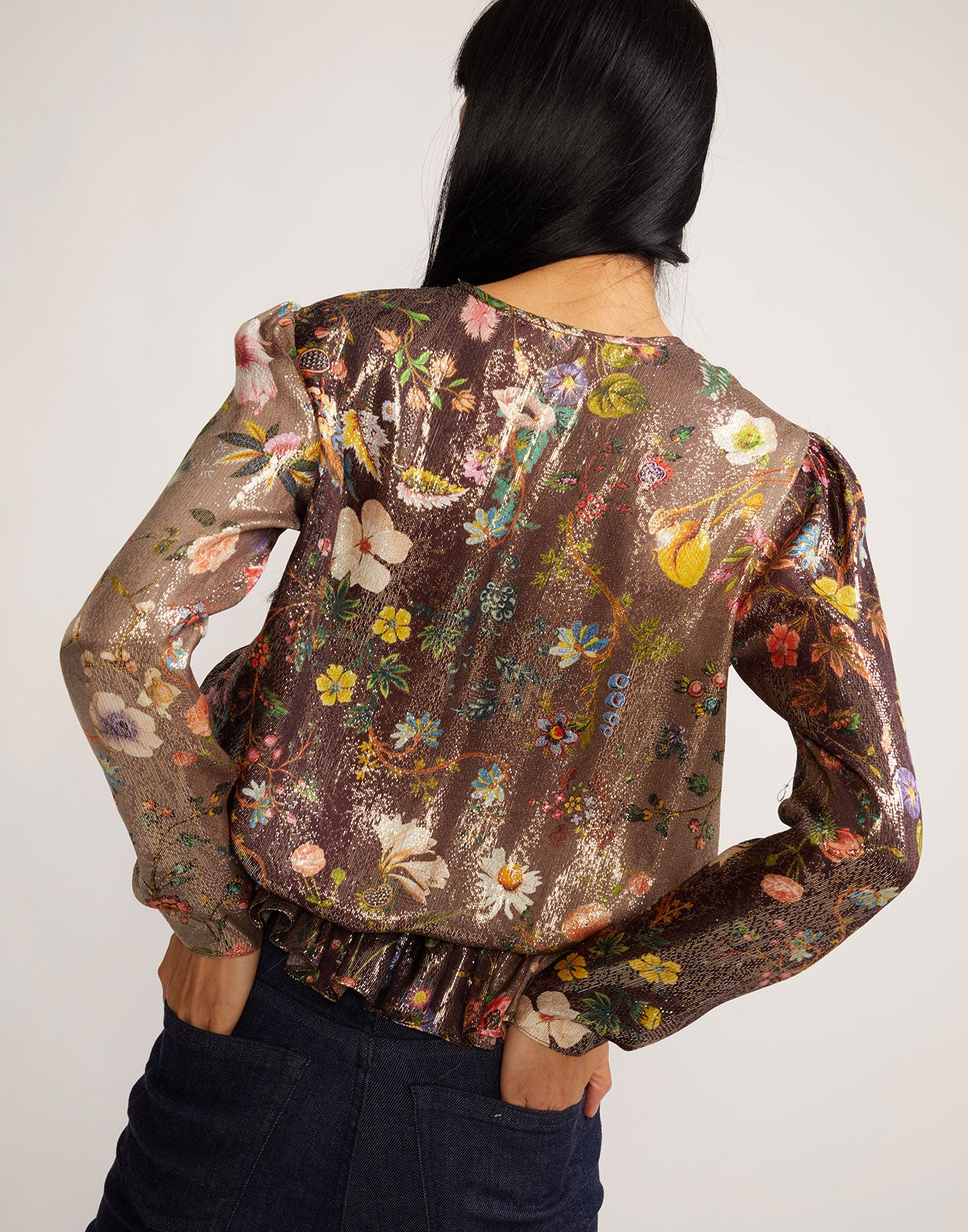 Back view of metallic floral blouse with ruching detail at waist.