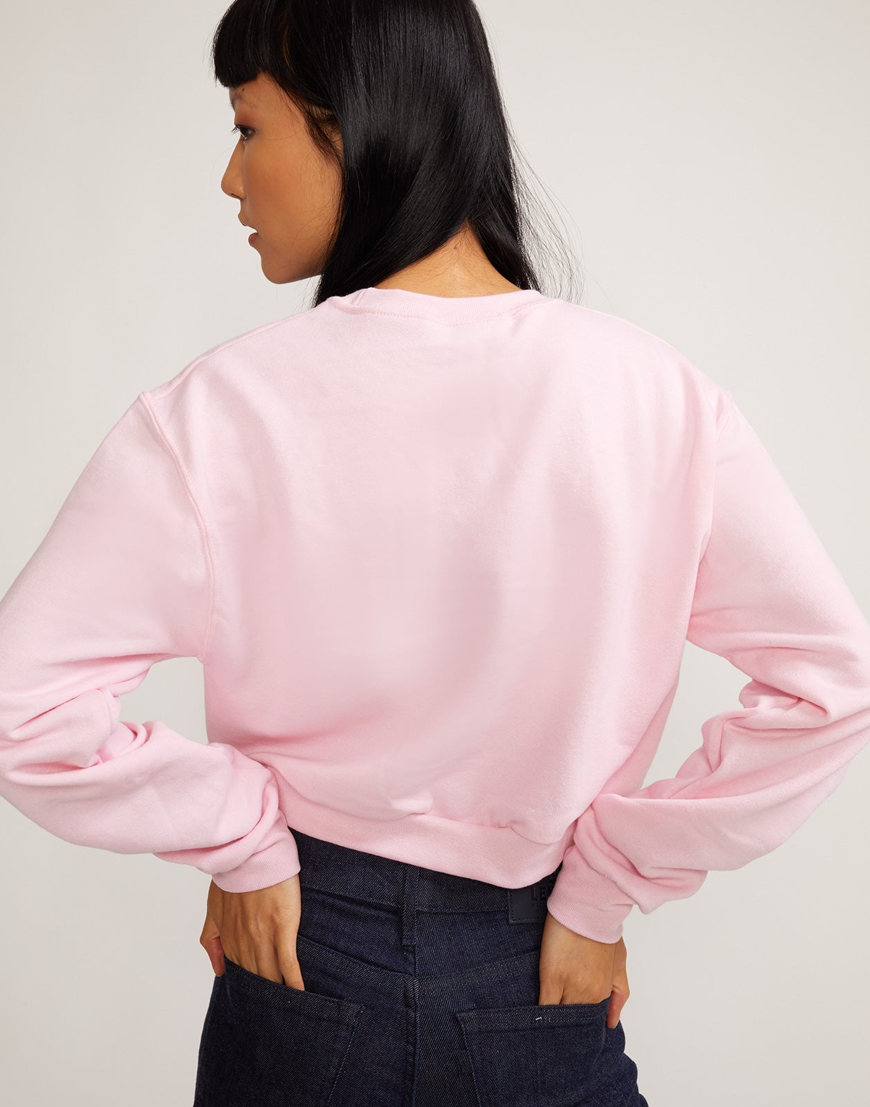 Back view of model wearing 'Role Model' cropped crewneck sweatshirt.