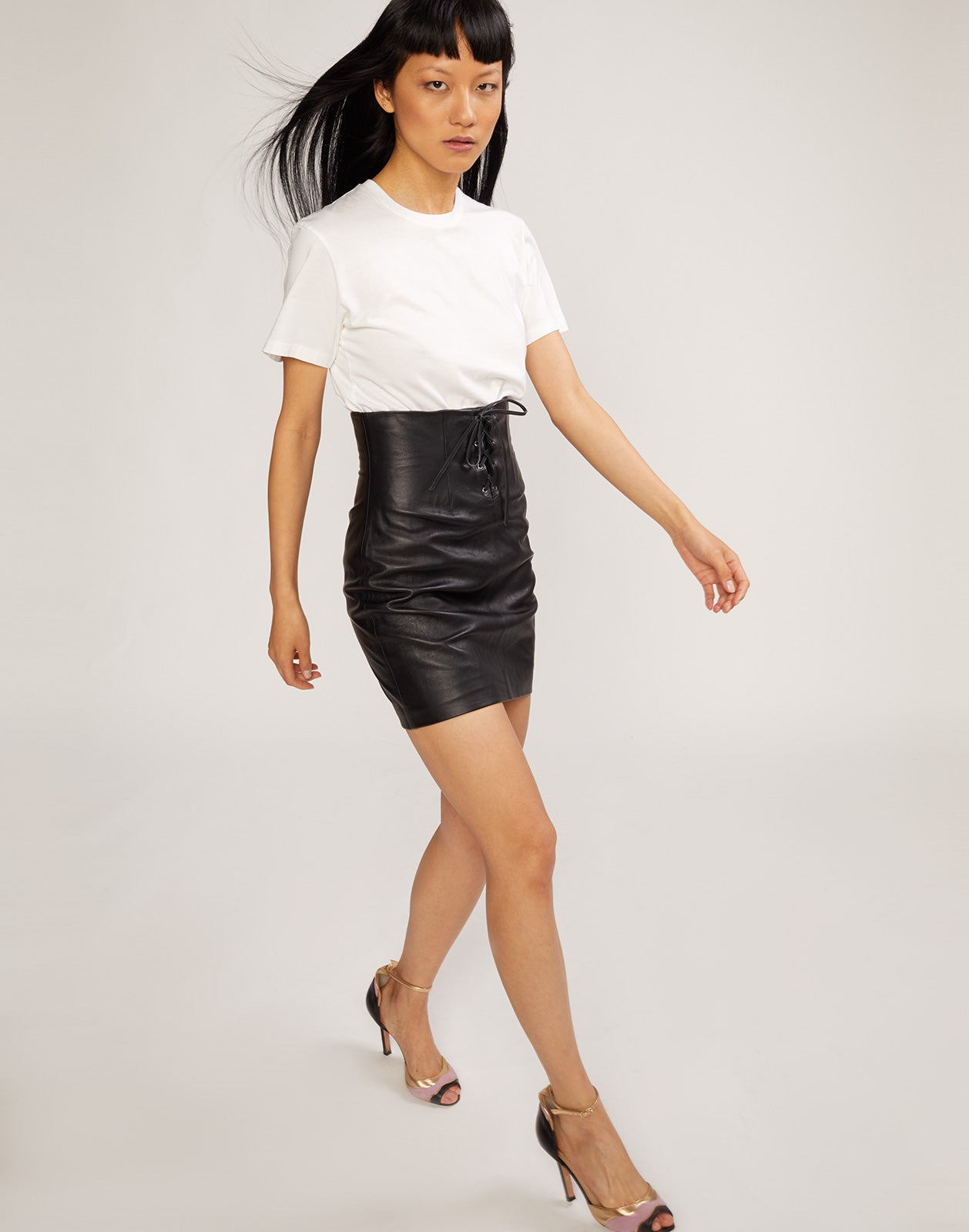 Full length view of model walking lace front, high waisted, leather skirt.