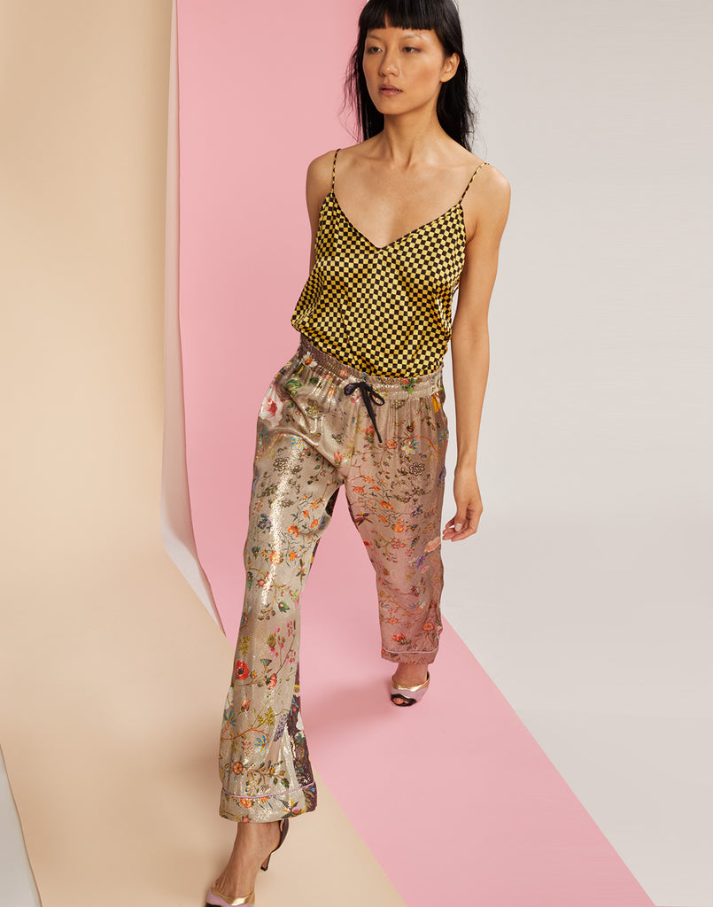 Diagonal walking shot of garden ombre print pants in metallic fabric
