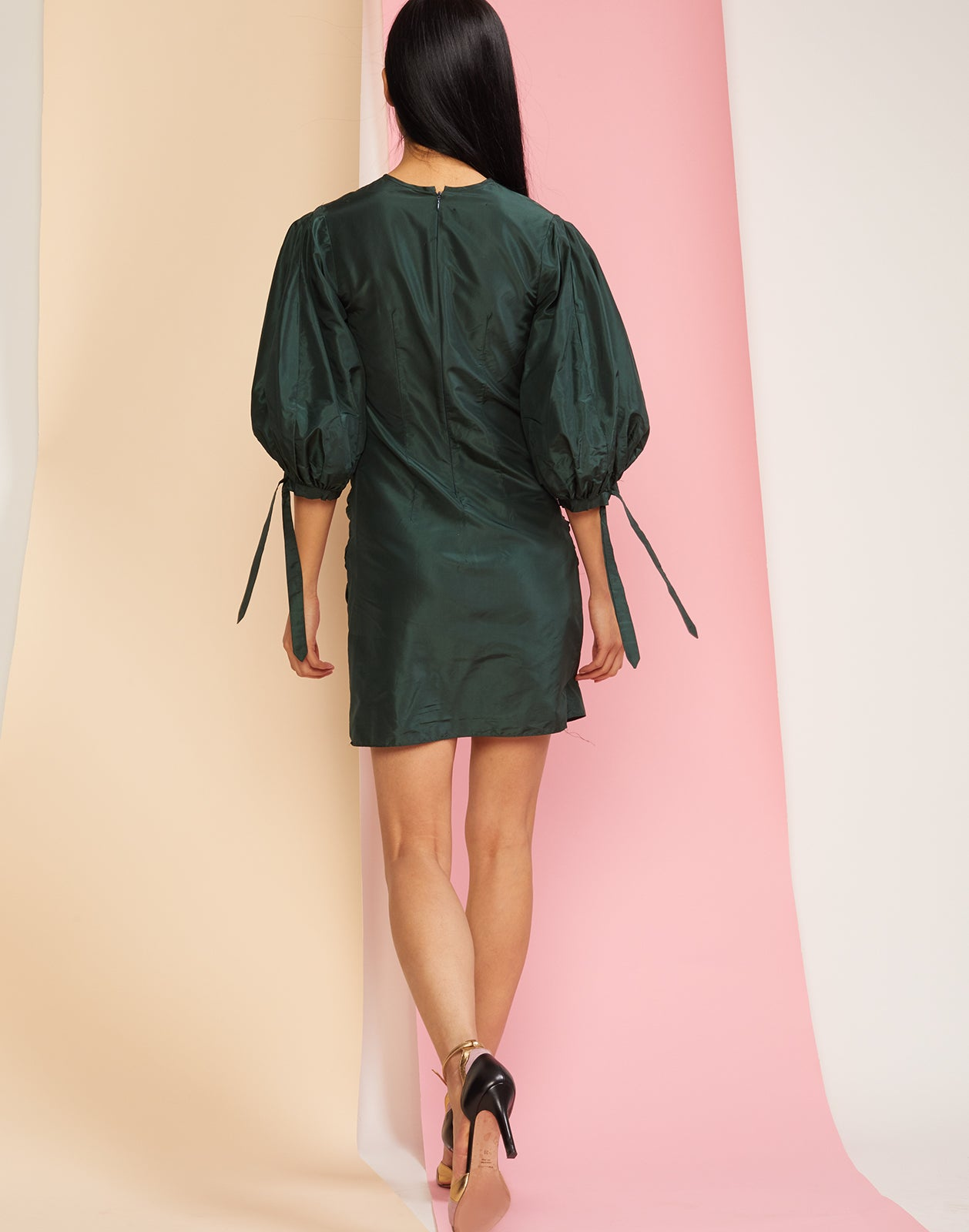 Back view of the Andi mini dress with puff sleeves in emerald silk taffeta.