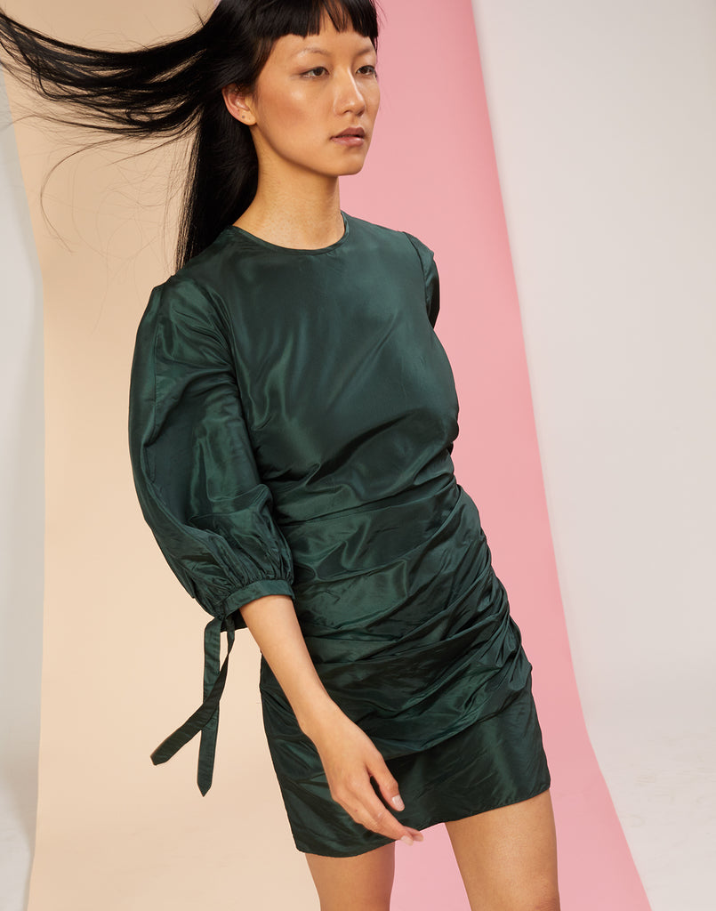 Close view of model walking in the Andi silk taffeta dress in emerald.